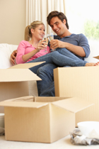 cohabiting couple unpacking after moving toasting with champagne